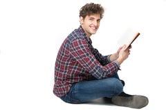 Uomo felice che si siede sul pavimento con il libro Immagini Stock
