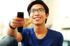 Uomo felice che si siede sullo strato che guarda TV Fotografie Stock Libere da Diritti