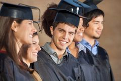 Uomo felice che sta con gli studenti sul giorno di laurea Immagini Stock