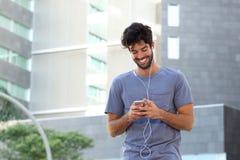 Uomo felice che sta nella città con le cuffie ed il telefono cellulare Fotografie Stock