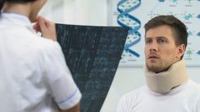 Uomo felice in collare cervicale della schiuma sull'appuntamento di medici, risultato positivo dei raggi x archivi video