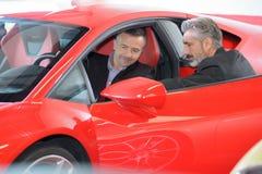 Uomo felice con il commerciante di automobile nell'esposizione automatica o in salone immagine stock libera da diritti