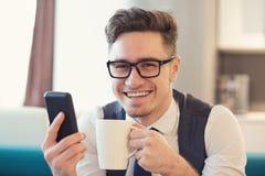 Uomo felice con il telefono e la tazza di caffè immagine stock libera da diritti