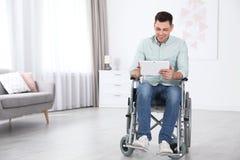 Uomo felice con la compressa che si siede in sedia a rotelle immagini stock