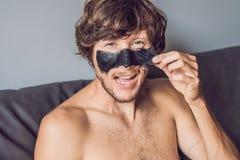 Uomo felice con la maschera nera sul fronte Uomo della foto che riceve i trattamenti della stazione termale Concetto di cura di p immagini stock libere da diritti