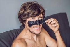 Uomo felice con la maschera nera sul fronte Uomo della foto che riceve i trattamenti della stazione termale Concetto di cura di p immagine stock libera da diritti