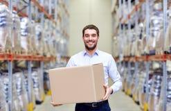 Uomo felice con la scatola del pacchetto del cartone al magazzino Immagini Stock Libere da Diritti