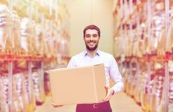 Uomo felice con la scatola del pacchetto del cartone al magazzino Immagine Stock Libera da Diritti