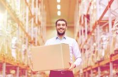 Uomo felice con la scatola del pacchetto del cartone al magazzino Fotografia Stock Libera da Diritti