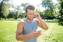 Uomo felice con le cuffie e lo smartphone al parco Fotografia Stock
