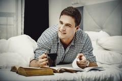 Uomo felice con un libro nel suo letto Fotografia Stock