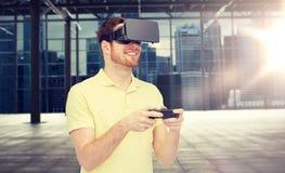 Uomo felice in cuffia avricolare di realtà virtuale con gamepad Immagine Stock