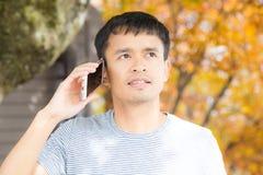 Uomo felice dei pantaloni a vita bassa che cammina nel parco di autunno facendo uso del telefono cellulare fotografia stock