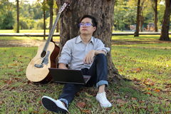 Uomo felice dei pantaloni a vita bassa che pende contro un albero con un computer portatile e una chitarra acustica Lui che guard fotografie stock