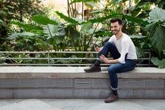 Uomo felice dei pantaloni a vita bassa in un parco facendo uso del telefono e del sorridere Youn moderno Fotografia Stock Libera da Diritti