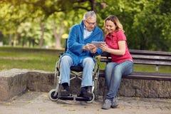 Uomo felice della sedia a rotelle con la figlia che per mezzo della compressa fotografia stock