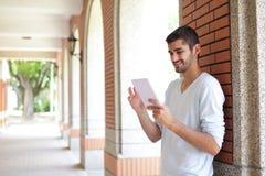 Uomo felice dello studente che per mezzo del cuscinetto di tocco Immagini Stock Libere da Diritti