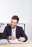 Uomo felice di affari che cattura le note Fotografie Stock Libere da Diritti
