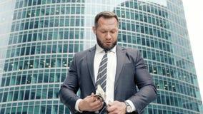 Uomo felice di affari che conta un batuffolo di contanti stock footage