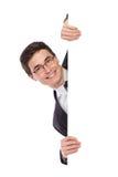 Uomo felice di affari che dà una occhiata dietro un'insegna. Immagine Stock