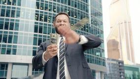 Uomo felice di affari che getta un pacchetto dei dollari nella via video d archivio