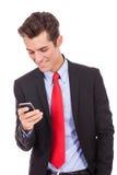Uomo felice di affari che legge uno SMS sullo smartphone Immagine Stock