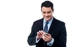 Uomo felice di affari che per mezzo del suo telefono cellulare Immagini Stock