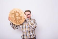 Uomo felice di affari che tiene grande bitcoin dorato su fondo bianco Valuta cripto, soldi virtuali, Internet e Immagini Stock Libere da Diritti