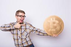 Uomo felice di affari che tiene grande bitcoin dorato su fondo bianco Valuta cripto, soldi virtuali, Internet e Fotografia Stock Libera da Diritti