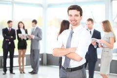 Uomo felice di affari con i colleghi alla parte posteriore Fotografie Stock Libere da Diritti