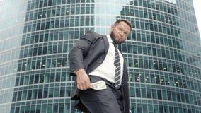 Uomo felice di affari con un batuffolo di contanti che si rallegra nel suo successo archivi video