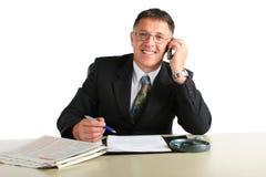 Uomo felice di affari occupato su un telefono, firmante un contratto e leggente le notizie finanziarie Fotografie Stock