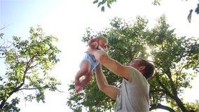 Uomo felice di medio evo che tiene il suo piccolo bambino, giovane padre che gioca con sua figlia stock footage