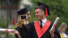 Uomo felice e donna in cappucci accademici ed abiti che filmano video sullo smartphone archivi video