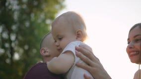 Uomo felice e donna che abbracciano infante all'aperto stock footage