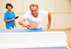 Uomo felice e donna maturi che giocano ping-pong fotografia stock