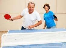 Uomo felice e donna maturi che giocano ping-pong immagine stock libera da diritti