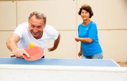 Uomo felice e donna maturi che giocano ping-pong immagini stock