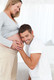 Uomo felice in ginocchio che ascolta la pancia della sua moglie immagine stock libera da diritti