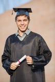 Uomo felice nel certificato della tenuta dell'abito di graduazione Fotografia Stock Libera da Diritti
