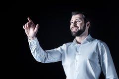 Uomo felice positivo che esamina lo schermo virtuale Immagini Stock