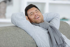 Uomo felice positivo che sorride sul sofà Fotografia Stock Libera da Diritti
