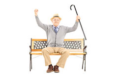 Uomo felice senior che si siede su un banco e che gesturing felicità Immagini Stock Libere da Diritti