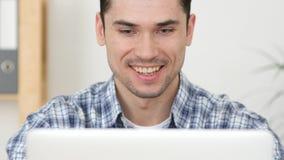 Uomo felice sul lavoro, lavorante al computer portatile Immagini Stock