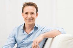 Uomo felice sul sofà Fotografia Stock Libera da Diritti