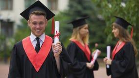 Uomo felice in vestito accademico che mostra diploma per la macchina fotografica e che ride, successo archivi video