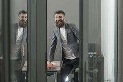 Uomo felice in vestito casuale al posto di lavoro Dell'uomo di sguardo porta barbuta della stanza fuori Uomo d'affari sicuro in u Fotografia Stock Libera da Diritti