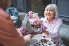 Uomo femminile anziano sorridente di riunione con i fiori Fotografia Stock Libera da Diritti