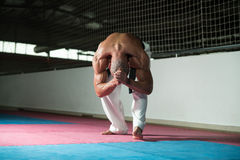 Uomo flessibile che allunga prima della formazione Fotografia Stock