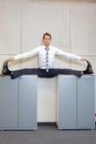 Uomo flessibile nel centro, posizione spaccata di affari sui gabinetti Fotografia Stock Libera da Diritti